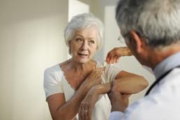 Patient showing doctor her frozen shoulder pain