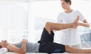 Physiotherapist massaging leg of man