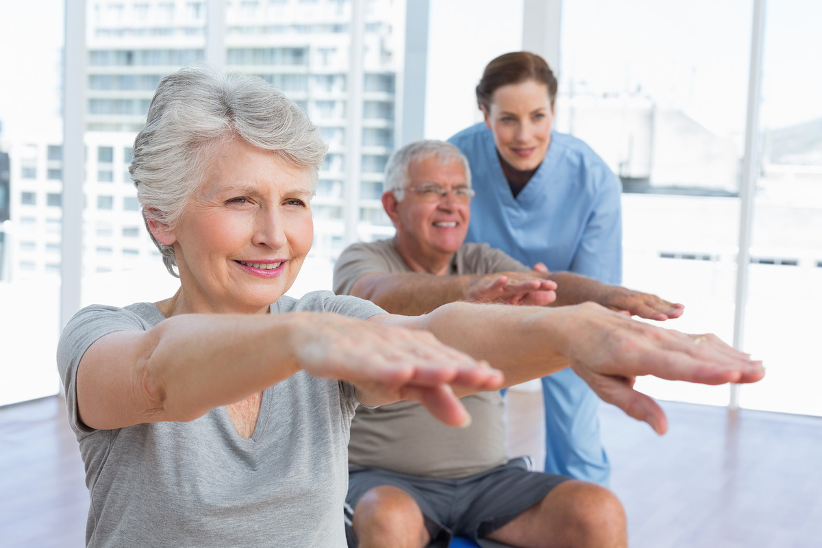 Female therapist assisting senior couple with exercises in the m