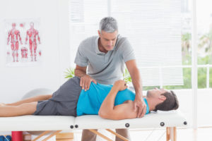 Doctor stretching a young man back in medical office