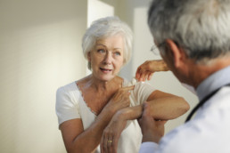 Patient showing doctor her frozen shoulder pain