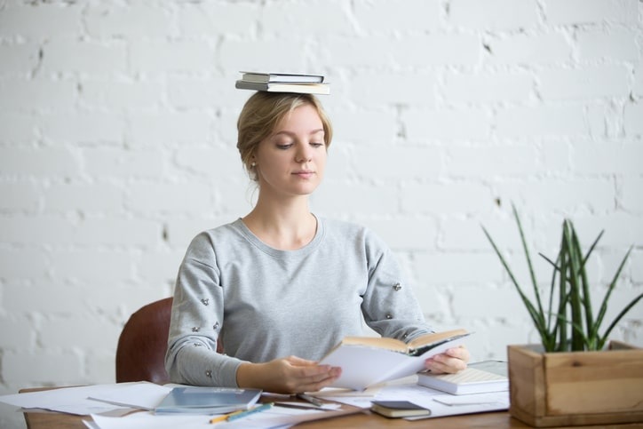 Portrait of attractive woman at desk, books on her head, showing good posture