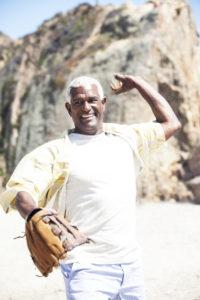 Senior man with a healthy rotator cuff throwing a baseball on the beach