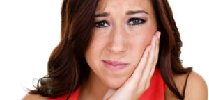 Closeup of a woman holding her swollen jaw for a TMJ and TMD concept
