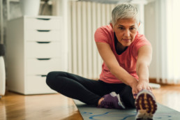 Mature woman exercising at home. Sitting on exercise mat and working extremity stretches on her legs.
