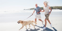 Senior couple running on the beach with a dog