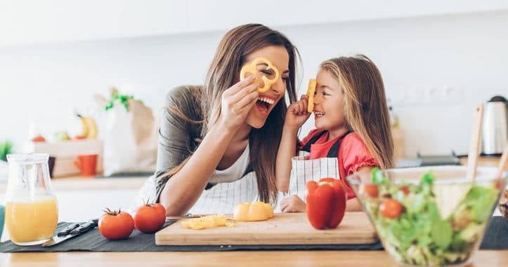 Mother teaching her daughter about healthy eating while having fun with the vegetables in the kitchen.