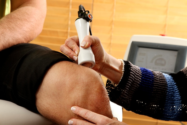 A physical therapist treating a patient with laser therapy on the knee