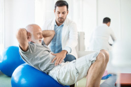 Closeup side view of a senior man having physical therapy for his sciatica with an expert doctor