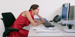 Side view of a female office worker slouching with bad posture and looking at notes on computer monitor at desk, cause of neck pain concept