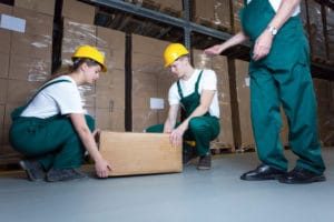 Two young workers lifting heavy box in warehouse. this can cause Work-Related Musculoskeletal Disorders