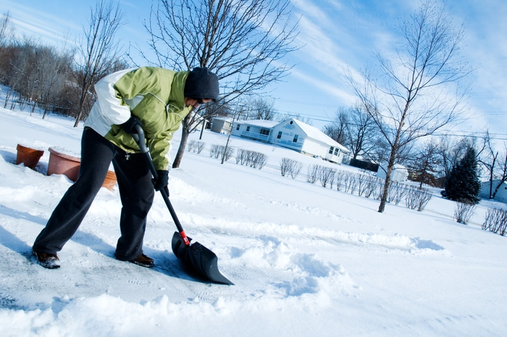 Woman shoveling the driveway after a winter snow. winter injuries concept