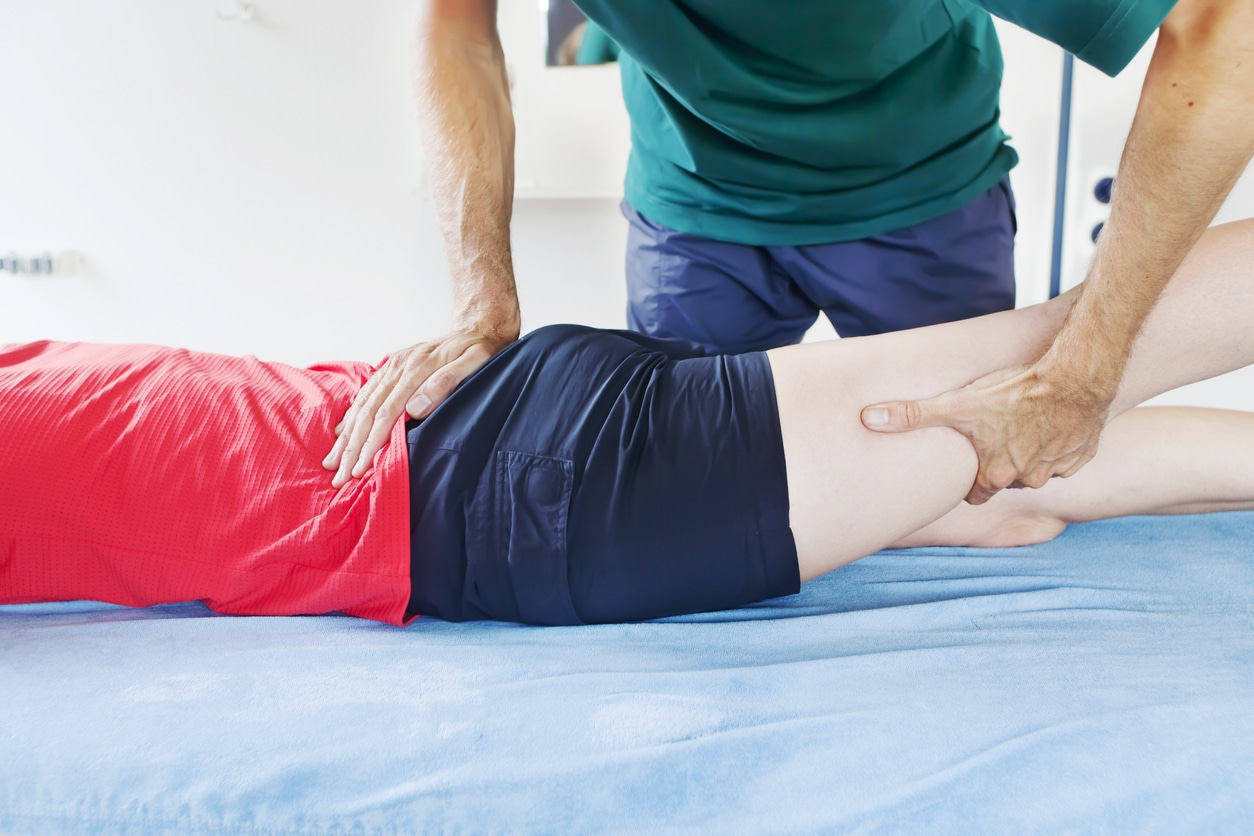 Physical therapist with a patient laying on table with sciatica nerve pain in lower back buttocks and leg