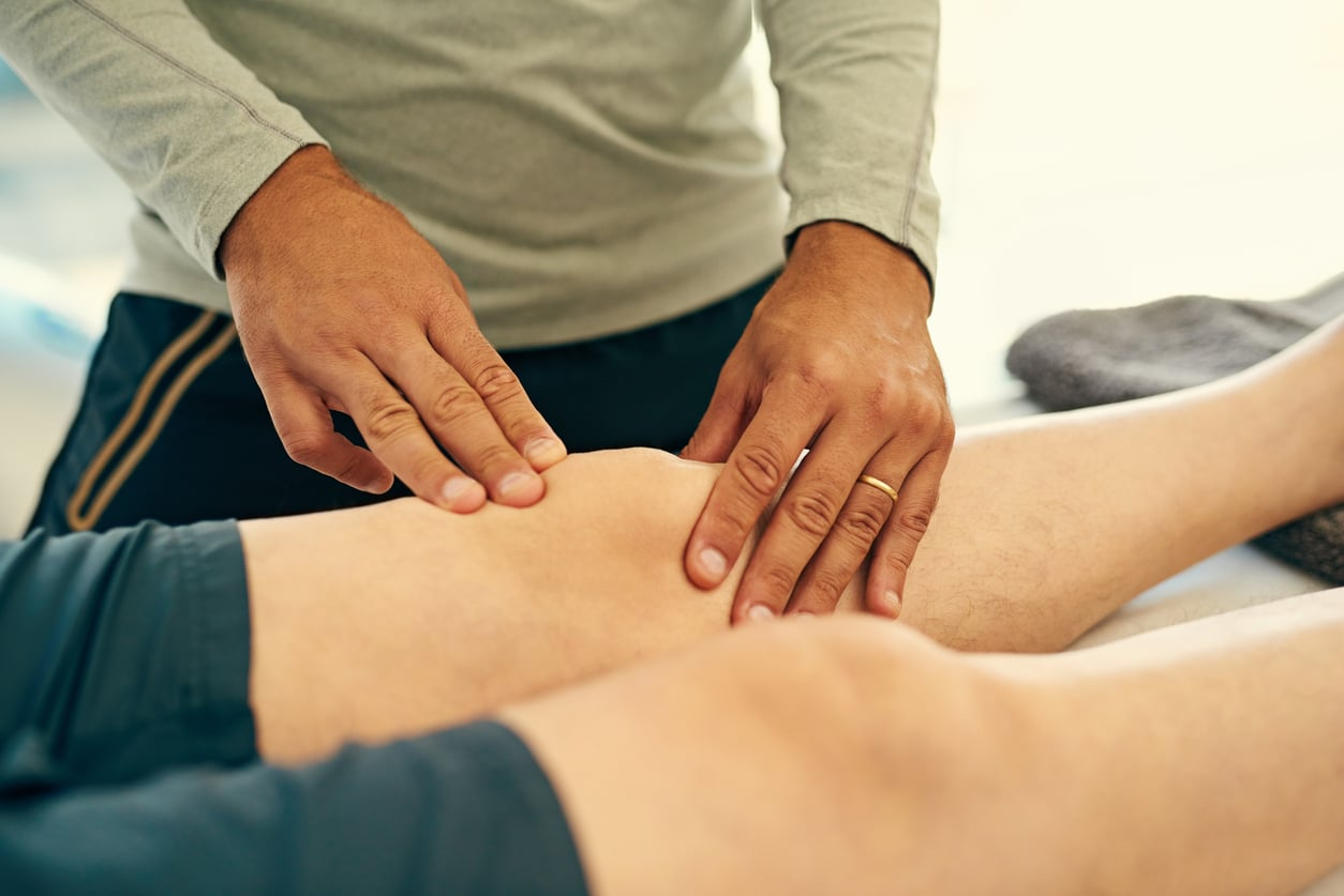 physical therapist using the Graston Technique to massaging his patient's knee