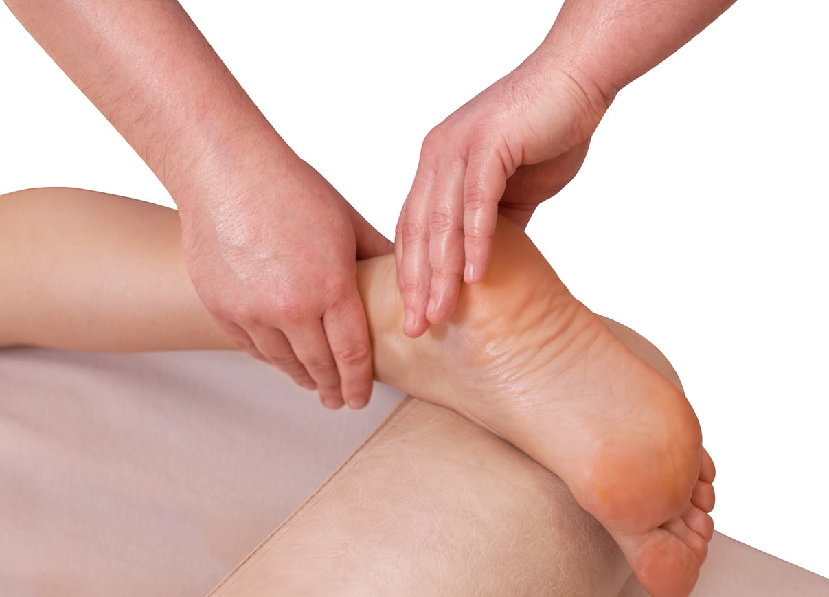 The doctor-podiatrist does an examination for Plantar fasciitis and massage of the patient's foot in the clinic.