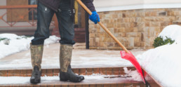 Man in rubber boots shoveling snow from the steps of the brick staircase with a large red plastic shovel