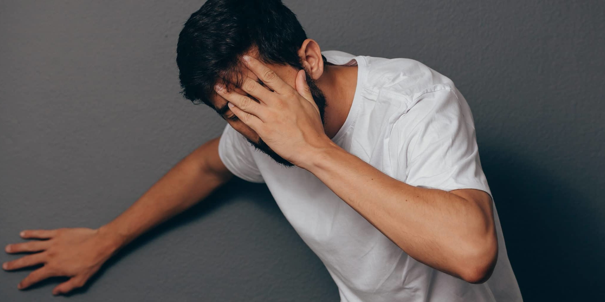 Man suffering from dizziness with difficulty standing up while leaning on wall. BPPV concept