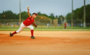 young pitcher throwing a fast ball / 11-12 years old league. Throwing injuries concept
