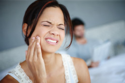 Shot of a woman sitting on the side of her bed with jaw pain with her boyfriend in the background. may be experiencing a condition known as Bruxism.