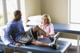 A female physical therapist examining a young African American man on a treatment table. He is sitting on the table with his legs stretched out in front of him. The physical therapist, a senior woman, is examining his knee. They are both looking at his bent knee with serious expressions on their faces. ACL injuries concept
