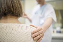 Doctor is standing with hand on senior woman's shoulder. Shoulder Bursitis concept