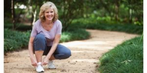 Senior woman with lower back pain bending down to tie shoelaces