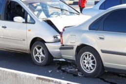 Two cars in a car accident on street. Insurance case - closeup damaged automobiles after collision in city. Car accidents