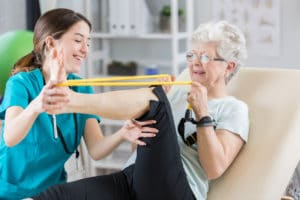 Confident physical therapist helps senior patient use resistance band. The woman is stretching out her leg. knee pain concept
