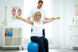 Senior woman sitting on fitness ball holding dumbbells being assisted by her physiotherapist in medical room. Rotator cuff injury concept