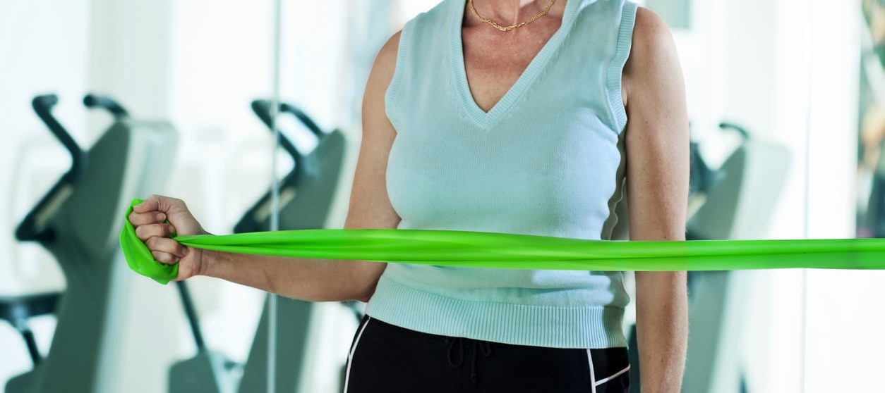 Woman doing internal and external rotator cuff exercises for shoulder injuries using a thera-band. This exercise is done to help recover from rotator cuff injuries. Horizontal shot.