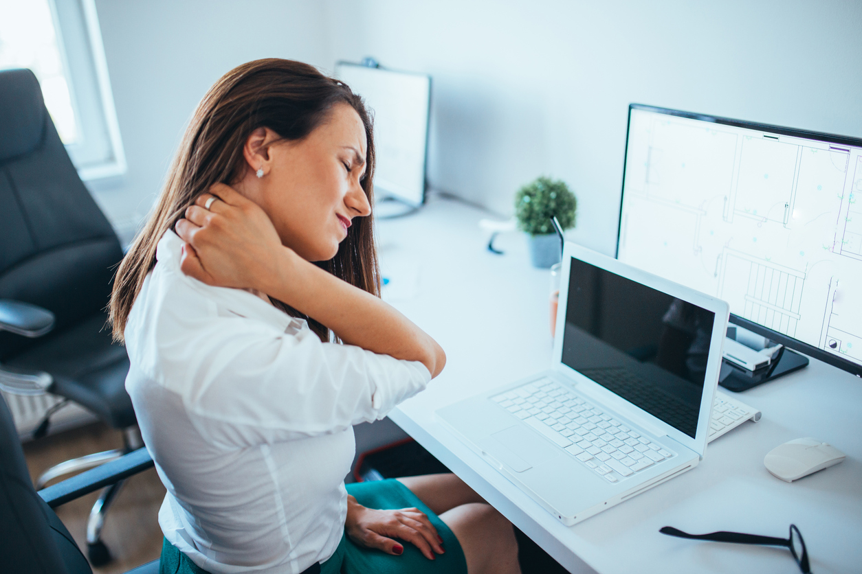 Young Businesswoman Suffering From Neck pain at an office desk