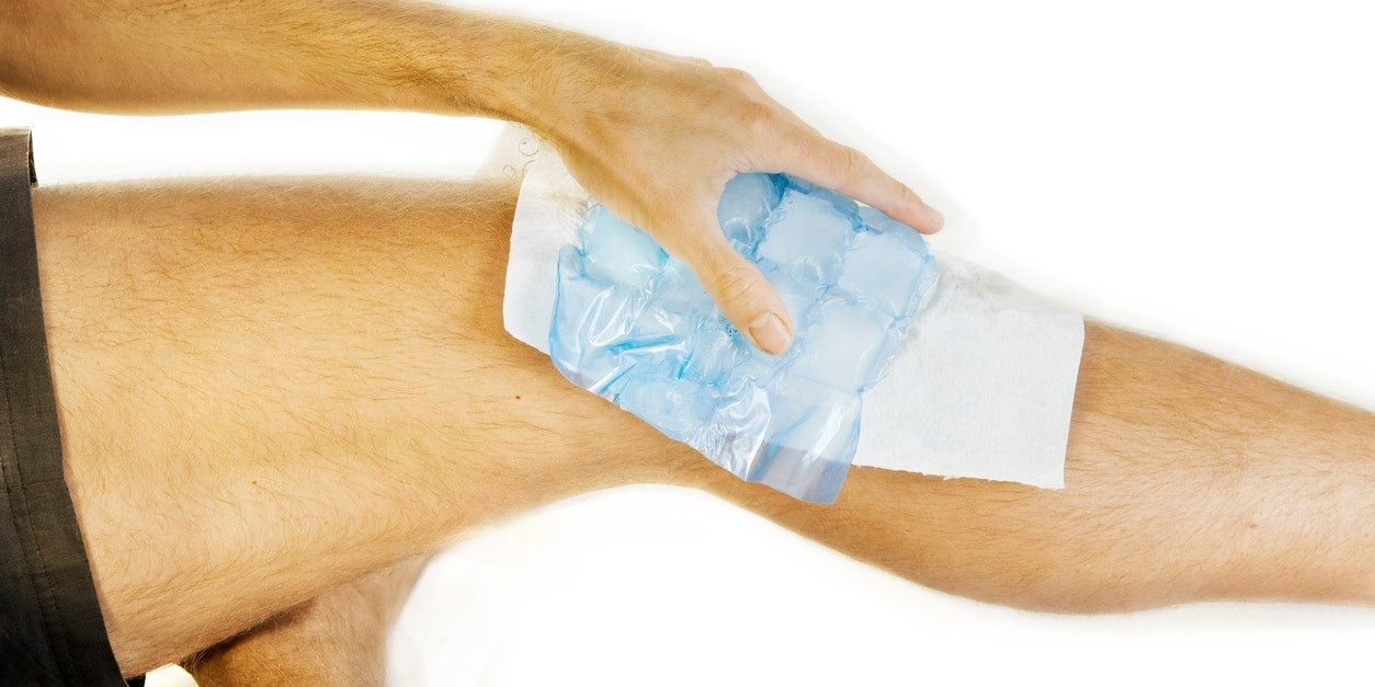 Lots of ice on an aching knee joint. A sheet is placed between ice and skin. A hand is holding the ice. XXL size image. RICE method