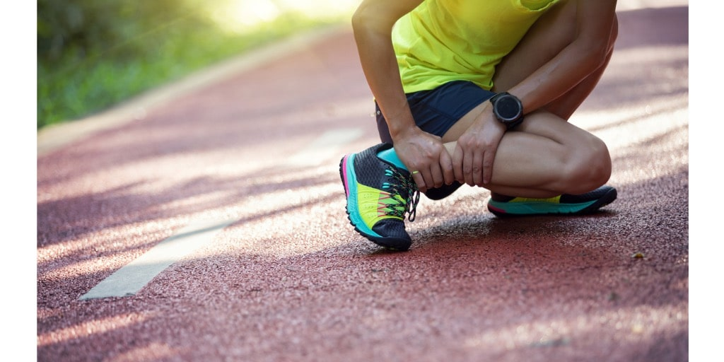 female runner suffering with pain from shin splints - sports running injury