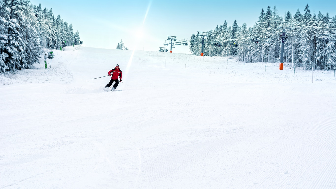 Skier skiing downhill in high mountains ski slopes