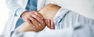knee pain - senior man with a physical therapist