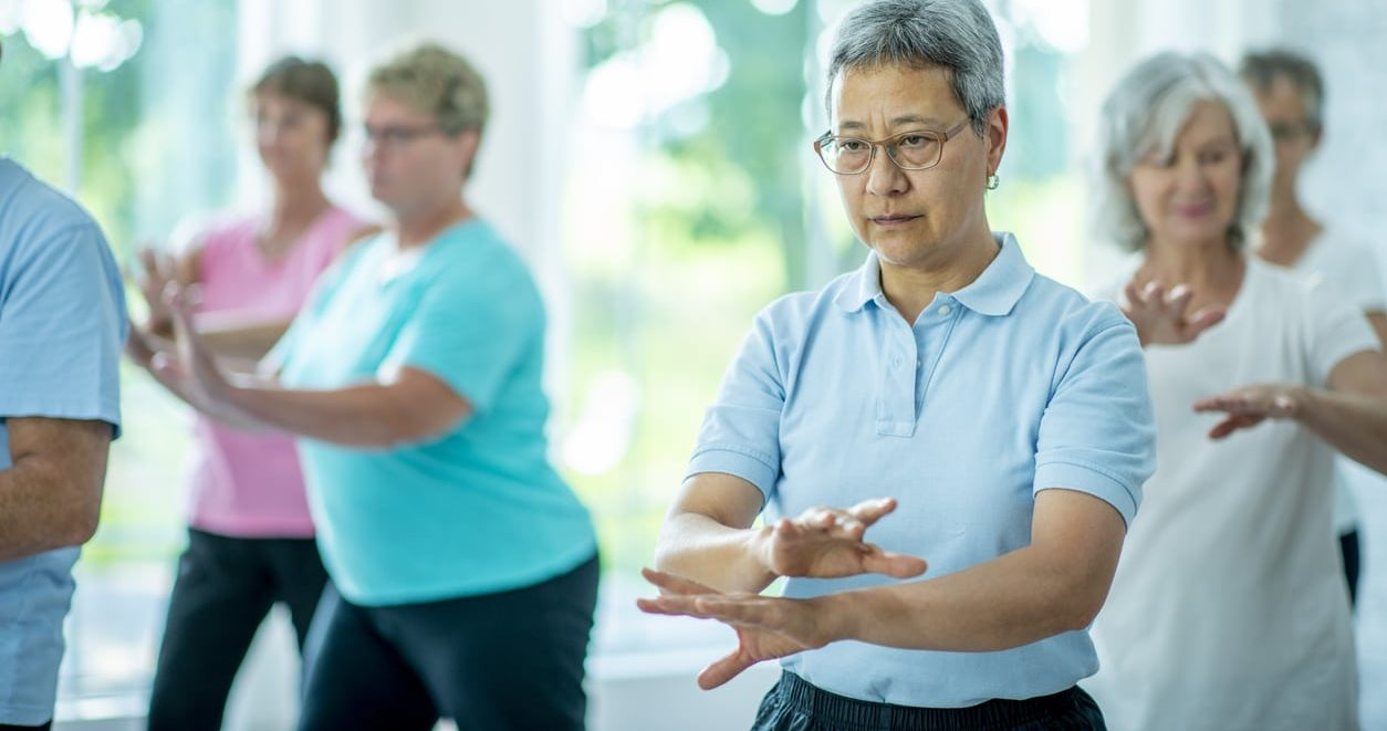 A group of senior individuals are indoors. They are performing the tai chi technique of meditation to attain mental and physical wellbeing.