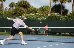 retired senior couple playing tennis at the club