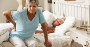 Woman getting out of bed with lower back pain