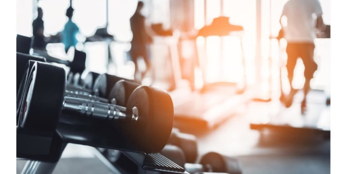 Rows of dumbbells in the gym with hign contrast and monochrome color tone with people on treadmills in the background. aerobic vs anaerobic exercise concept