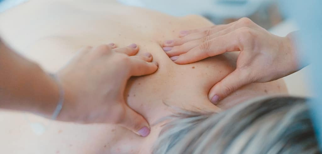 physical therapist massages a patients back as a tool for relieving back pain