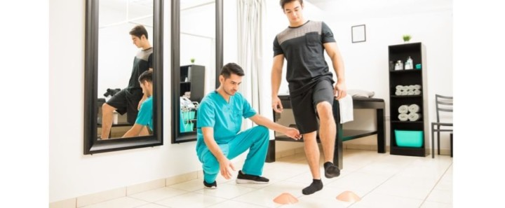 Physical Therapist Motivating Male Patient To Walk Between Cones for Balance