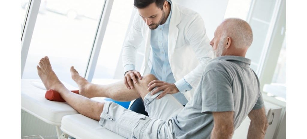 Senior man with a physical therapist. He is looking for a Baker's Cyst due to knee pain