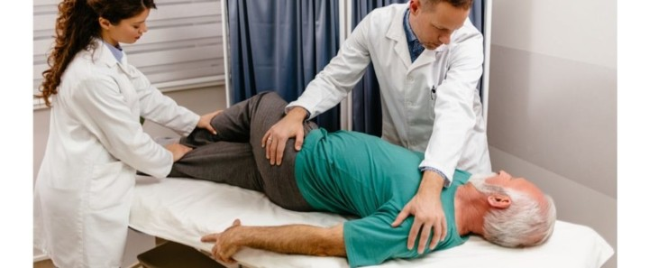 Senior man getting natural relief for sciatic pain with a physical therapist