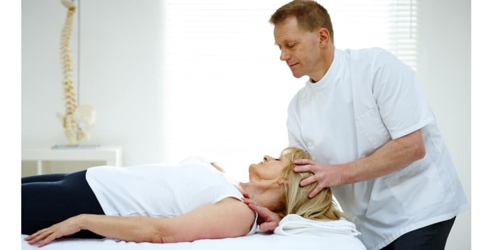 Physical therapist adjusting neck muscles of patient with headaches