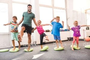 Four children doing balancing exercises with an instructor