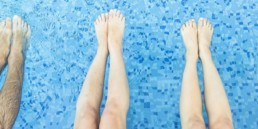 Legs view of friends relaxing and chilling in swimming pool showing different lengths in legs that may cause back pain