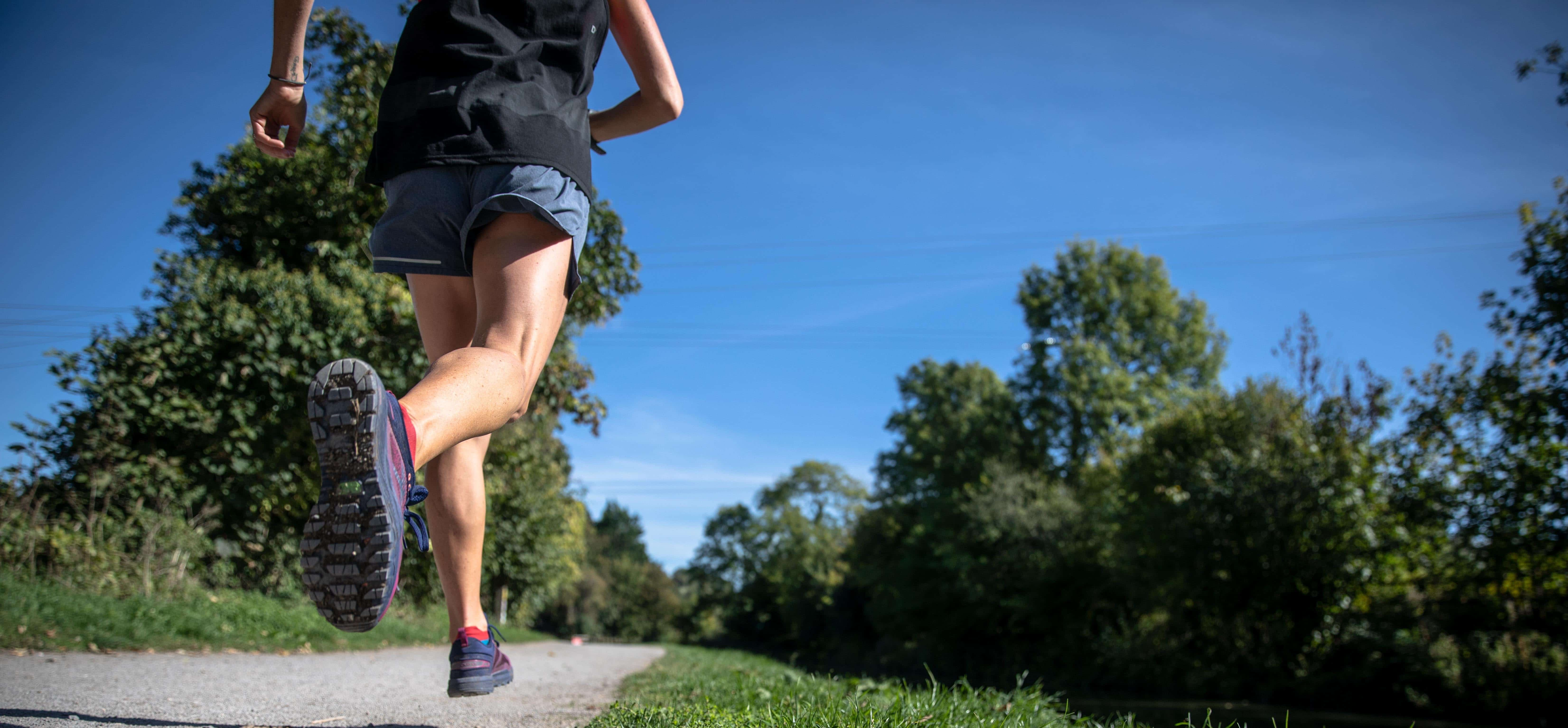 tips for runners like this woman running on a sidewalk is the summer outdoors