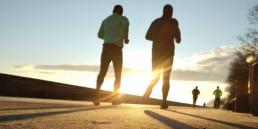 Two senior men running early in the morning sunrise in background