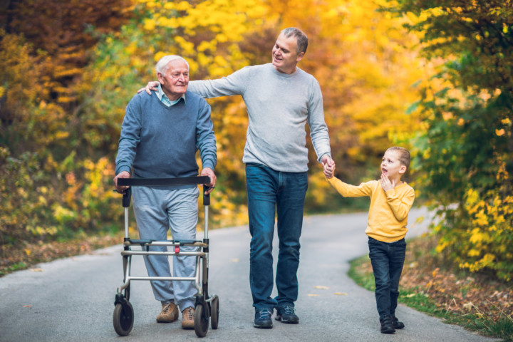 Elderly father adult son and grandson out for a walk in the park and avoiding a fall risk with a walker