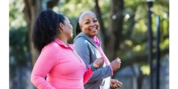 Two mature women power walking outdoors and smiling. Good exercise to make your workouts more intense.